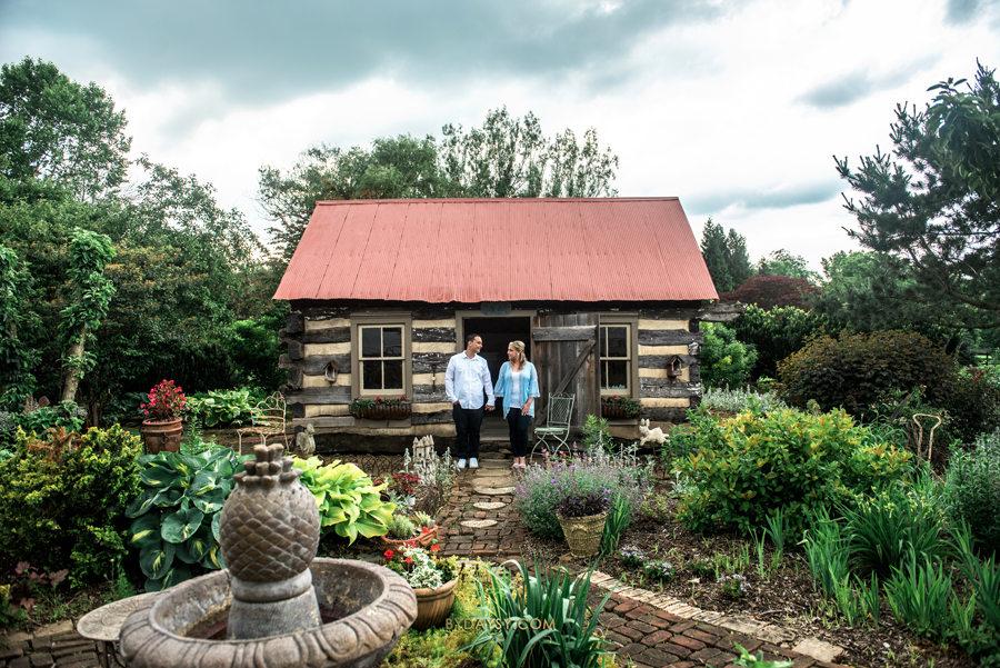 couple in front of a rustic house in Surreybrooke with nature and a fountain