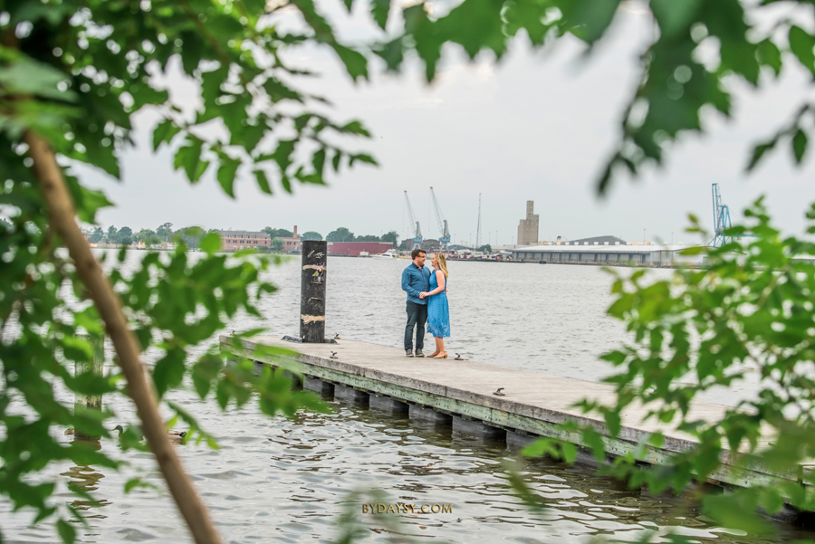 couple on focus standing at the pier among leaves