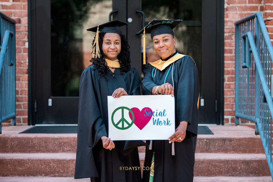 2 graduating students holding a sign we love social work