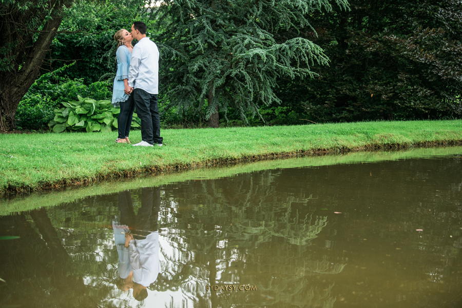 bride to be and groom to be kissing each other by the lake in Surreybrooke