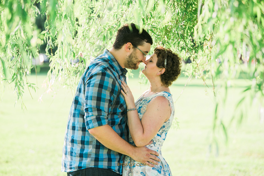 bride to be and groom to be kissing under the tree baker park leaves on top of the couple