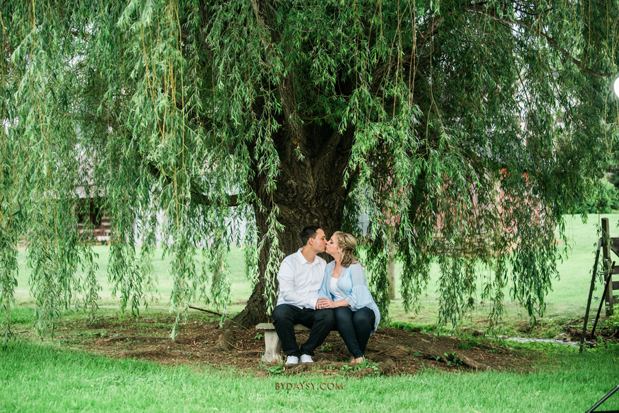 bride to be and groom to be seating under the tree and kissing