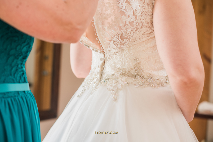maid of honor helping bride to get ready bottom wedding dress