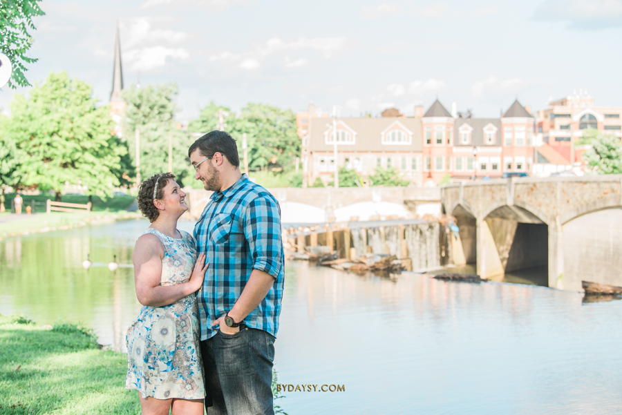 couple looking to each other with bridge in the back in Frederick