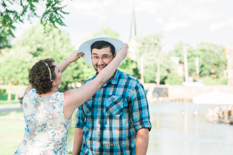 bride to be putting her hat on her fiance at Baker Park Frederick