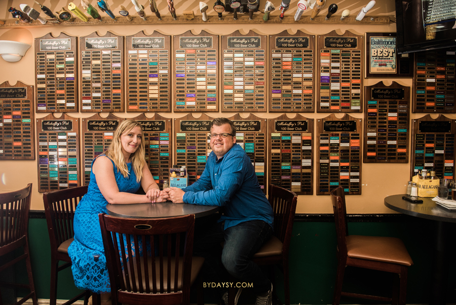 couple seating at the table in a craft beer bar with names on the wall behind them