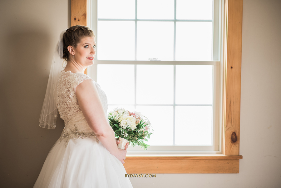 bride standing close to window holding bouquet of flowers