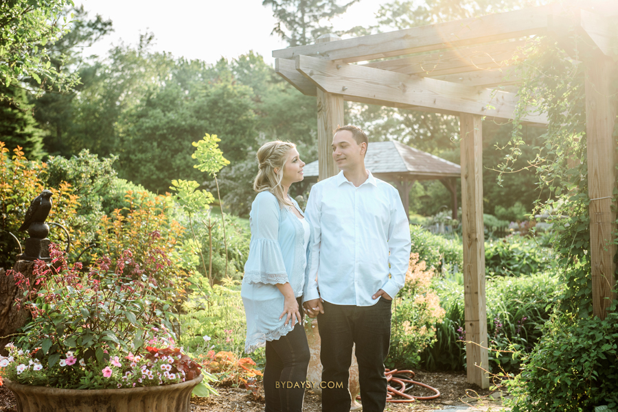 bride to be and groom to be looking to each other surrounded by flowers in Surreybrooke
