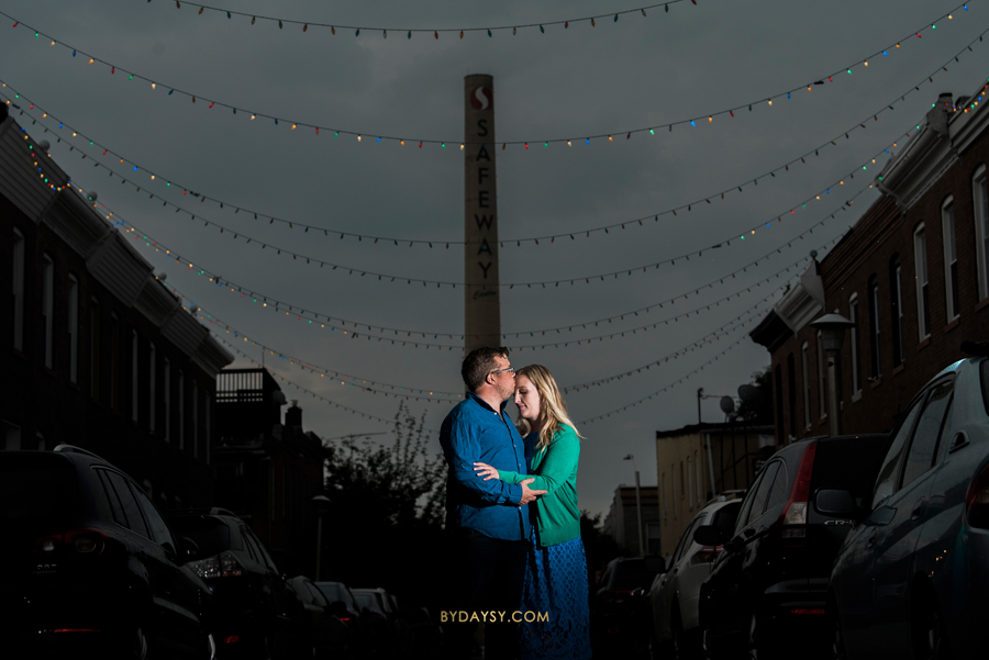 couple standing at night with string lights hanging