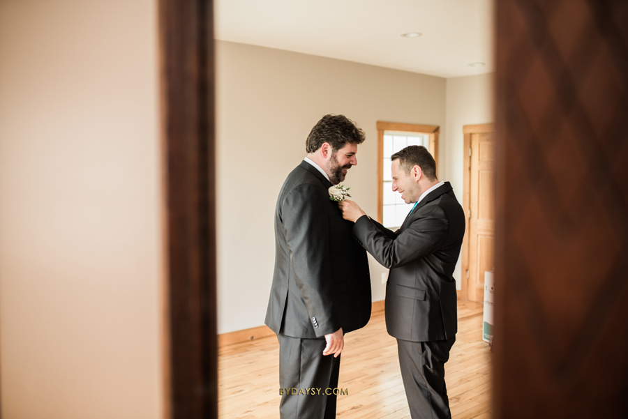 best man helping groom to fix his tie