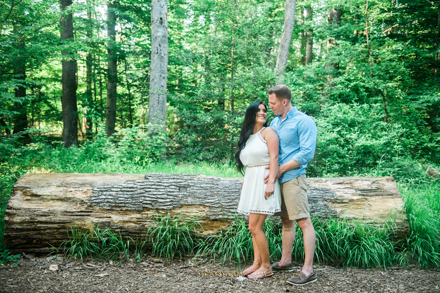 couple looking to each other with a big tree trunk in the back at green spring gardens park alexandria VA