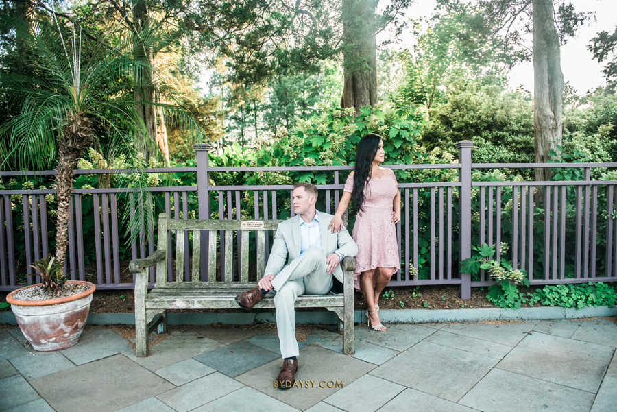 groom to be seated on a bench while bride to be is touching his shoulder at green spring gardens park alexandria VA