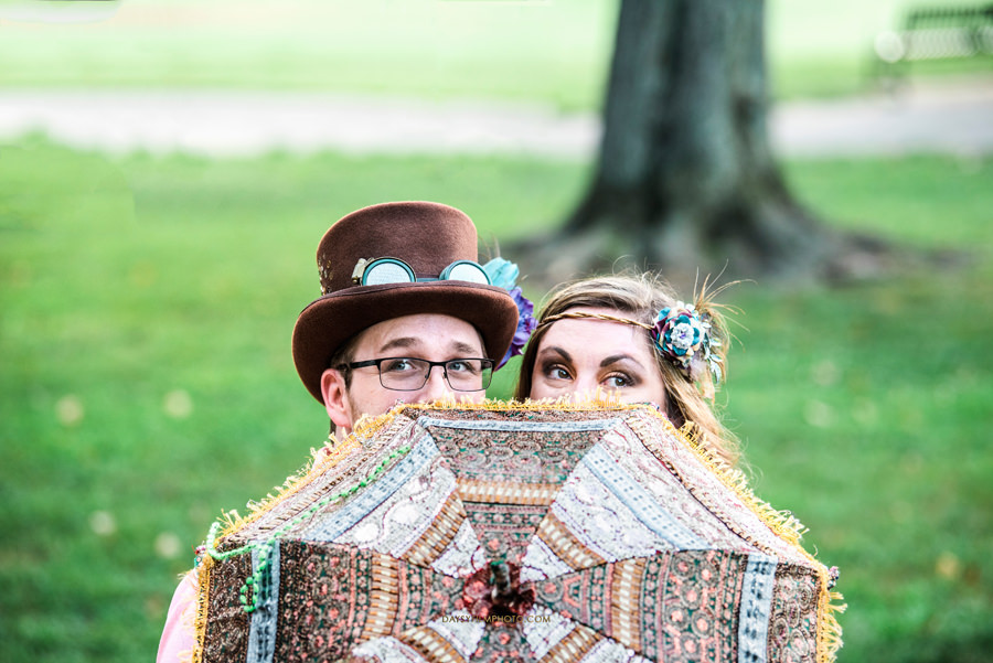 couple hiding behind fun umbrella at baker park in maryland