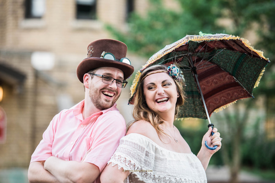 couple laughing with props umbrella and hat at baker park maryland