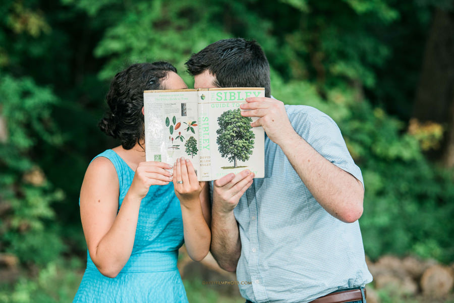 couple kissing each other behind a nature book at Rust Nature Sanctuary