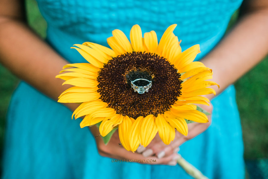 bride to be holding a sunflower with the engagement ring