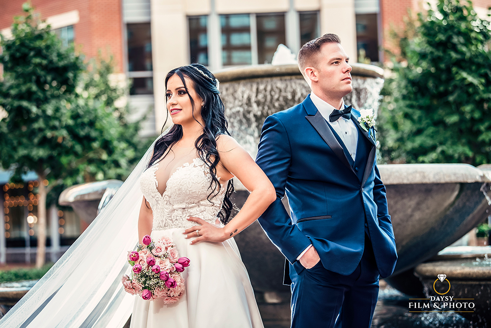 modern bride and groom standing in front of fountain