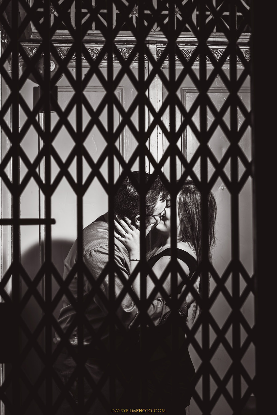 couple kissing at old elevator engagement photo at Bromo Seltzer Arts Tower, in Baltimore MD