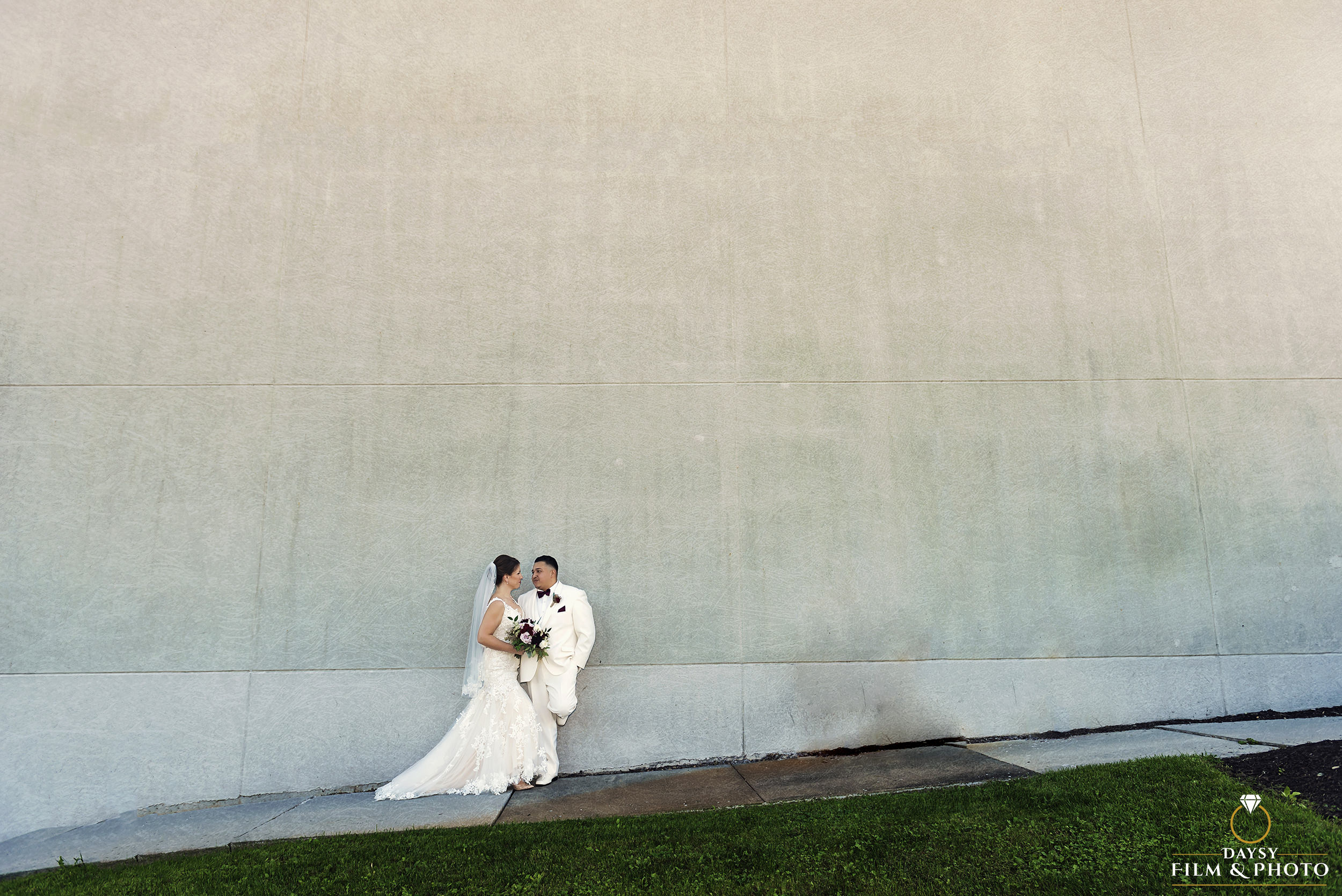 bride and groom standing on a white wall