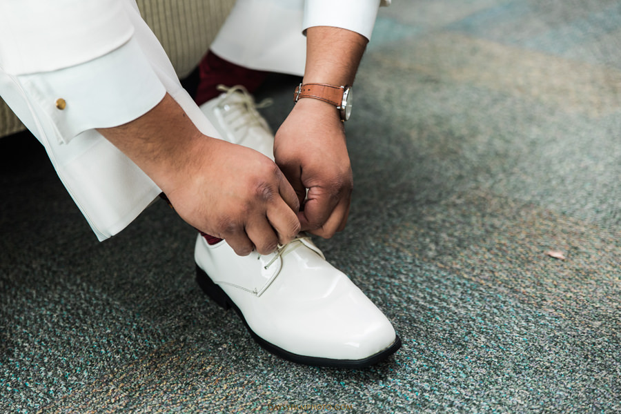 groom wearing white tuxedo and white shoes for wedding