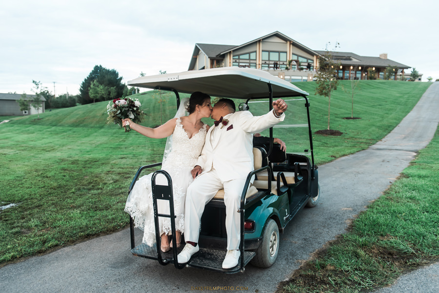 bride and groom cheering up on gold cart ride