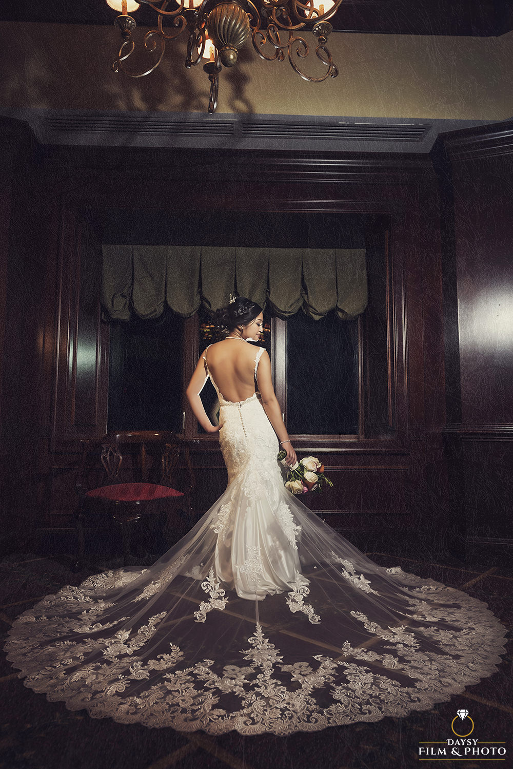 beautiful luxury bride on her wedding dress holding flowers down portrait