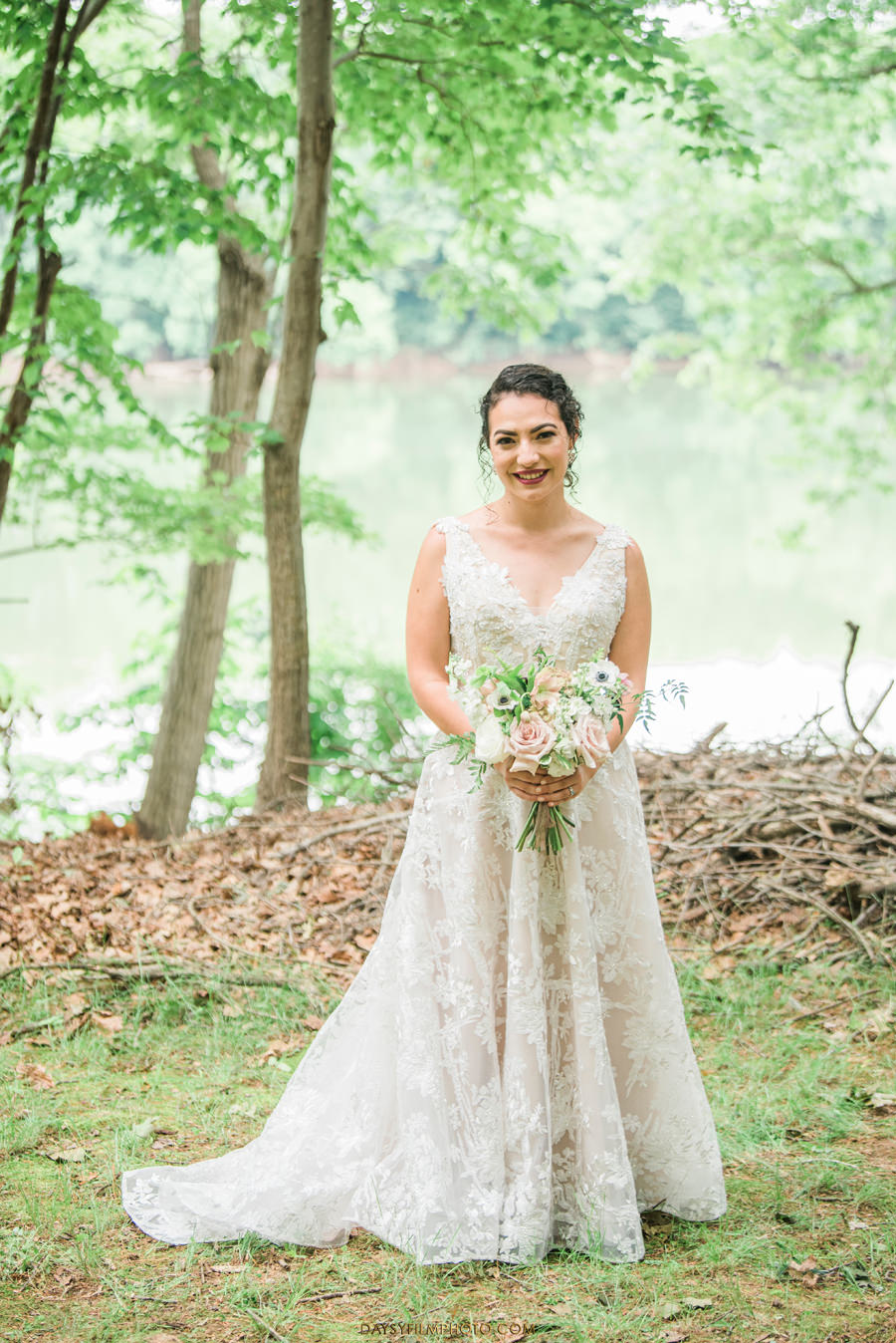 The Woodlands at Algonkian Wedding bride holding bouquet by the water