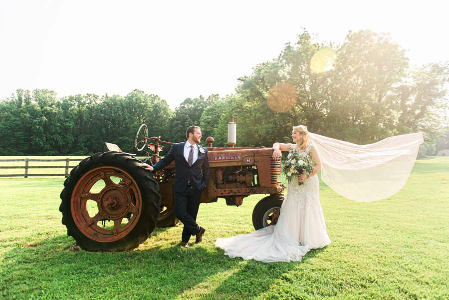 Vineyard of Mary's Meadow bride and groom in front of tractor
